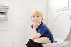 Cute little boy in restroom. Toddler child trainig use toilet. Hygiene for little child royalty free stock images