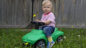 Cute little boy riding a green machine. Cute little boy riding on a green machine in the yard of a country house royalty free stock photo