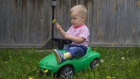 Cute little boy riding a green machine. Cute little boy riding on a green machine in the yard of a country house stock images