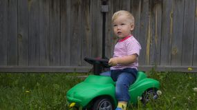 Cute little boy riding a green machine. Cute little boy riding on a green machine in the yard of a country house stock photography