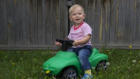 Cute little boy riding a green machine. Cute little boy riding on a green machine in the yard of a country house stock photos