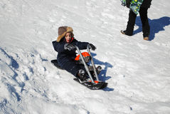 Cute little boy riding motorcyle in the snow outdoors. Royalty Free Stock Photography