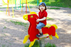 Cute little boy on rocking horse outdoors in summer Stock Photos