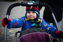 Cute little boy rolls baby stroller on the street royalty free stock photography