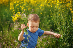 Cute little boy running with a bouquet of flowers on a yellow me Royalty Free Stock Photo