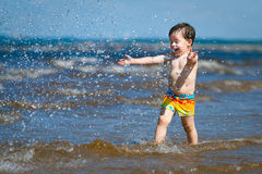 A cute little boy running through the wate Stock Photography