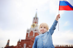 Cute little boy with russian flag with Spasskaya tower Russia, Moscow on background. Patriotic feeling/patriotism concept royalty free stock image