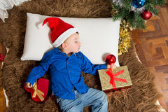 Cute Little boy in Santa Claus hat sleeping on Rug Stock Image