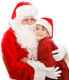 Cute Little Boy With Santa. Cute little boy gives Santa Claus a big hug. Isolated on white stock image