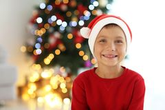 Cute little boy in Santa hat on blurred  background. Cute little boy in Santa hat on blurred background Stock Images