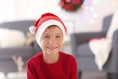 Cute little boy in Santa hat on blurred  background. Cute little boy in Santa hat on blurred background Stock Image