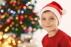 Cute little boy in Santa hat on blurred  background. Cute little boy in Santa hat on blurred background Stock Photos