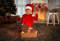 Cute little boy in Santa hat with Christmas present. At home Stock Photos