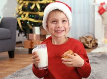 Cute little boy in Santa hat drinking milk and eating delicious cookie. At home Stock Photography