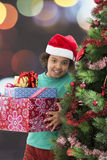 Cute little boy in santa hat holding gift near Christmas tree. Royalty Free Stock Images