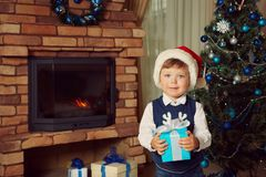 Little boy in santa hat holding a gift. Cute little boy in santa hat holding a gift near Christmas tree. child with present. xmas kid Royalty Free Stock Images