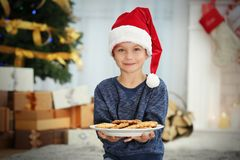 Cute little boy in Santa hat with plate of delicious cookies. At home Stock Photography