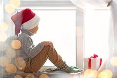 Cute little boy in Santa hat sitting on windowsill  at home. Cute little boy in Santa hat sitting on windowsill at home Stock Photos