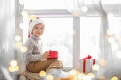 Cute little boy in Santa hat sitting on windowsill  at home. Cute little boy in Santa hat sitting on windowsill at home Stock Images