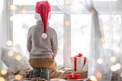 Cute little boy in Santa hat sitting on windowsill  at home. Cute little boy in Santa hat sitting on windowsill at home Royalty Free Stock Photo