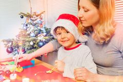 Boy preparing Christmas ornaments with his mom royalty free stock photo