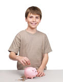 Cute little boy saving his money in a piggy bank Stock Image