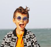Cute little boy at seacoast in fashion clothers and blue glasses Royalty Free Stock Photo