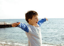 Cute little boy at seacoast gesturing like flying Stock Image