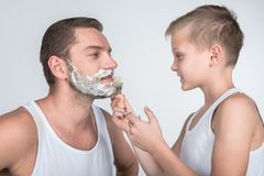 Father and son shaving together. Cute little boy shaving father with shaving foam isolated on grey Royalty Free Stock Photos