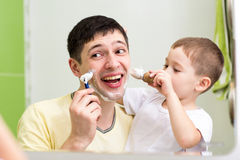 Cute little boy shaving his father in bathroom Royalty Free Stock Photos