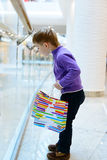 Cute little boy with shopping bags near handrail Royalty Free Stock Photography