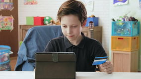 Cute little boy shopping online using entering credit card number using digital tablet and is happy after making a. Child in his room lifestyle Cute little boy stock footage