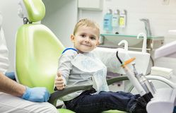 Cute little boy showing thumb up sign at dentist`s office clini. Cute little boy showing thumb up sign at dentist`s office  сlinic Royalty Free Stock Images