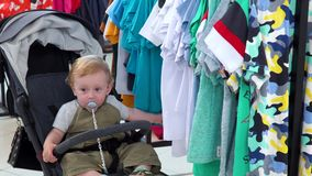 Cute little boy sit in baby buggy in a clothing store stock footage