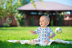 Cute little boy siting on green grass Stock Images