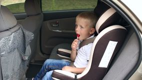 A cute little boy sits in a car seat in the car and eats a Lollipop. Slow motion. A cute little boy in a white t-shirt and jeans sits in a car seat in the car stock video