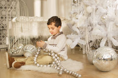 Cute little boy sits on a floor and plays with a big glass toy near the Christmas tree Stock Photo