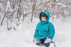 Cute little boy sits in a snow in park in the winter. A cute little boy sits in a snow in park in the winter Stock Photos
