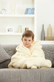Cute little boy sitting in bathrobe at home sofa Royalty Free Stock Photography