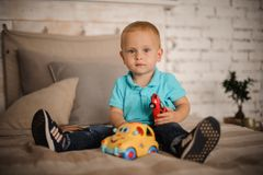 Cute little boy sitting on the bed with a car toy. Dressed in blue shirt and jeanes Royalty Free Stock Photo