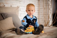 Cute little boy sitting on the bed with a toy. Dressed in blue shirt and dark vest Royalty Free Stock Photos
