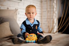 Cute little boy sitting on the bed with a toy in his hands. Dressed in blue shirt and dark vest Royalty Free Stock Photography