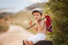 Cute little boy, sitting on a big old suitcase, vintage, holding. A bundle, eating bread and smiling Royalty Free Stock Images