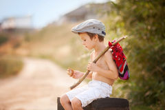 Cute little boy, sitting on a big old suitcase, vintage, holding. A bundle, eating bread and smiling Stock Photo