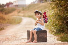 Cute little boy, sitting on a big old suitcase, vintage, holding Royalty Free Stock Photo