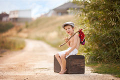 Cute little boy, sitting on a big old suitcase, vintage, holding. A bundle, eating bread and smiling Stock Photos