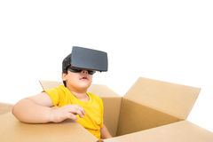 Cute little boy sitting in the box watching video on VR glasses Royalty Free Stock Images