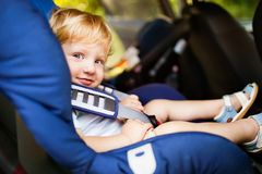Little boy sitting in the car seat in the car. Stock Images