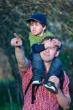 Cute little boy sitting on father's shoulders. Outdoors in city park stock photos