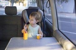 Little boy sitting in van and eating yogurt and orange juice Royalty Free Stock Image